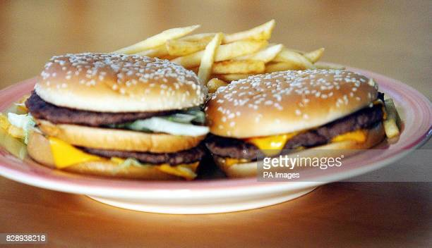 A generic shot of beef burgers in a sesame seed bun with chips on the side