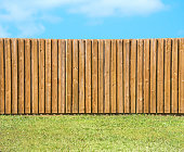 Generic wooden residential privacy fence with  a lush green grass yard in the foreground and a beautiful blue sky with fluffy clouds.