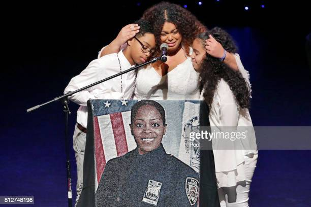 Genesis Villella center and twins Delilah and Peter Vega children of New York City Police Officer Miosotis Familia participate during her funeral for...