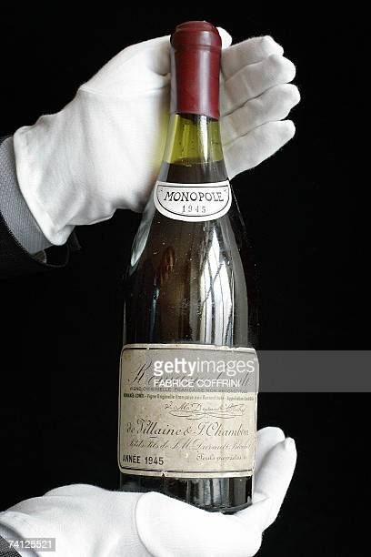 A Christie's employee displays a rare bottle of French 1945 vintage RomaneeConti wine 11 May 2007 during an auction preview in Geneva Only 600...