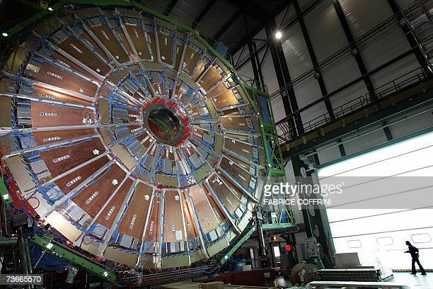 A woman passes 22 Mars 2007 near Geneva behind a layers of the world's largest superconducting solenoid magnet one of the experiments preparing to...