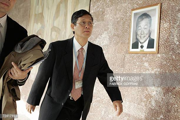Shigeru Omi of Japan candidate for the post of DirectorGeneral passes in front of a picture of former DirectorGeneral Lee Jong Wook who died after...
