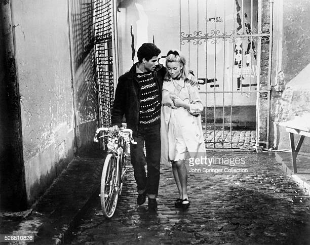 Genevieve Emery walks through a courtyard with Guy whom she loves but her mother has forbidden her to marry Released 1964