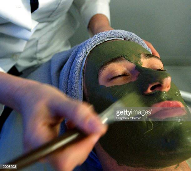 Genevieve paints a mud treatment on a client during a facial treatment at NICKEL spa for men May 16 2003 in New York City The spa which is the only...