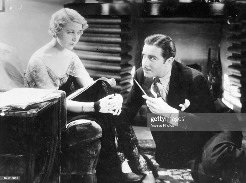 Genevieve Tobin sits in a chair while John Boles relaxes on the floor with a pencil in his hand in a scene from the film 'Seed' 1931