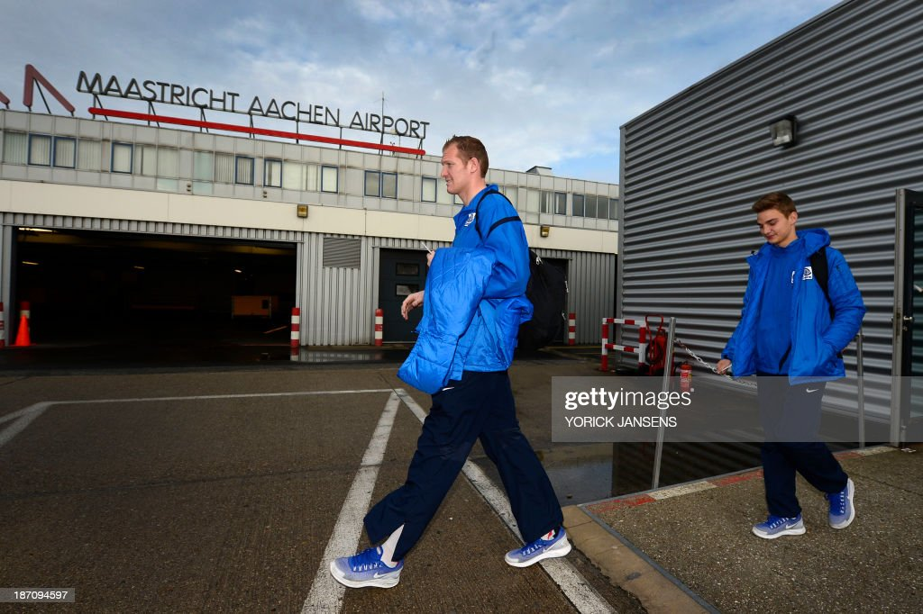 Genk goalkeeper Kristof Van Hout (L) and midfielder Pieter Gerkens get ready to board a plane on November 6, 2013 at Maastricht airport for Vienna on the eve of the team's Europa League Group G football match against SK Rapid Wien.