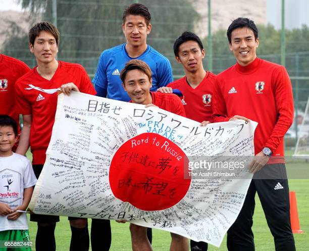 Genki Haraguchi Akihiro Hayashi Shu Kurata Hiroshi Kiyotake and Makoto Hasebe of Japan pose with the national flag with messeges of Japanese students...