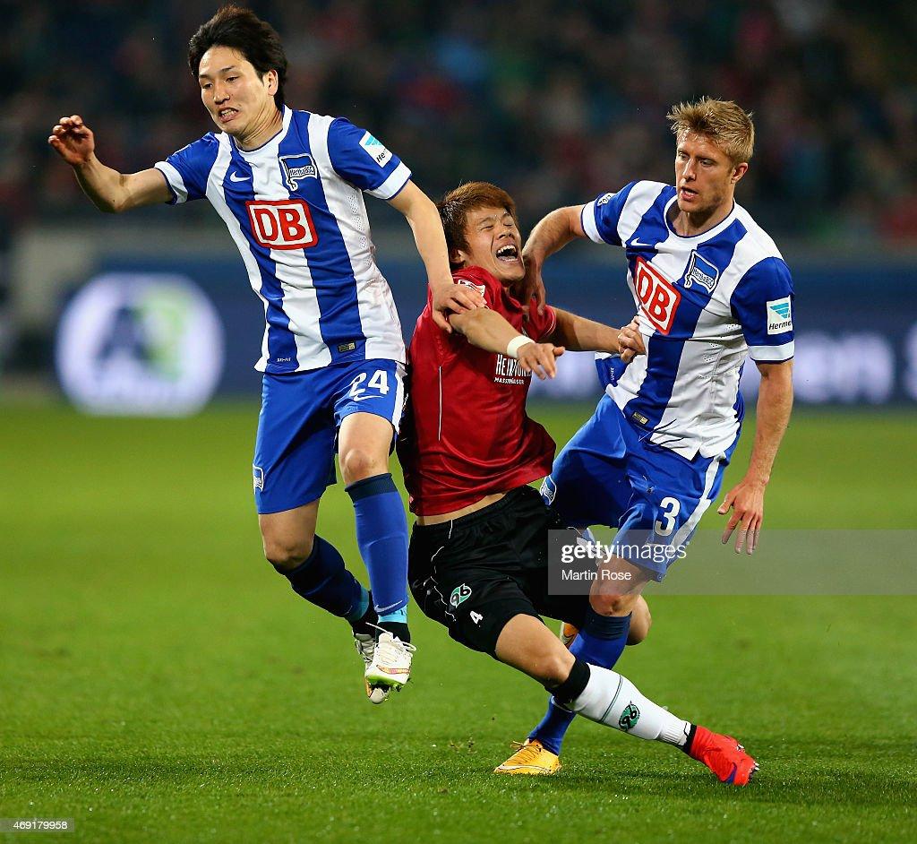 Genki Haraguchi and Per Ciljan Skjelbred of Hertha BSC challenge Hiroshi Kiyotake of Hannover 96 during the Bundesliga match between Hannover 96 and...