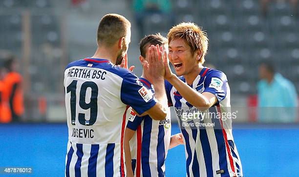 Genki Haraguchi celebrates with team mate Vedad Ibisevic after winning the Bundesliga match between Hertha BSC and Vfb Stuttgart at Olympiastadion on...