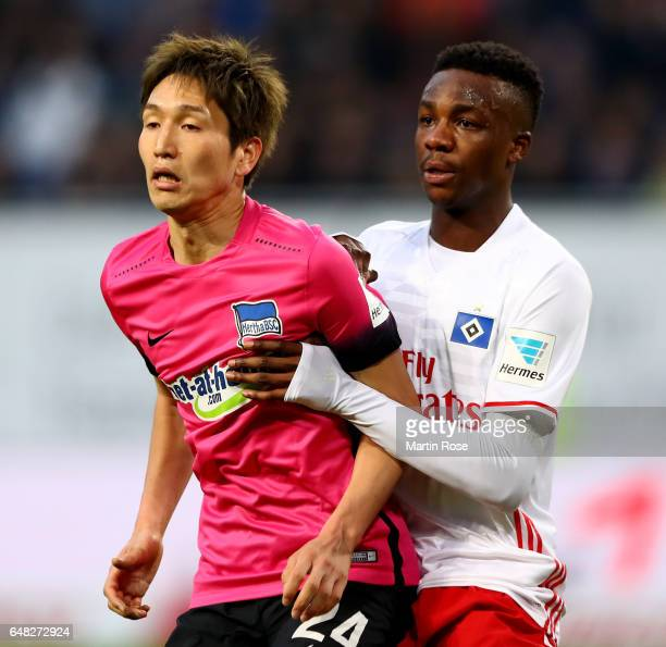 Genki Haraguchi of Berlin is challenged by Gideon Jung of Hamburg during the Bundesliga match between Hamburger SV and Hertha BSC at Volksparkstadion...