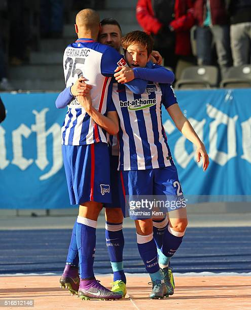 Genki Haraguchi of Berlin jubilates with team mate Vedad Ibisevic and John Anthony Brooks after scoring the first goal during the Bundesliga match...