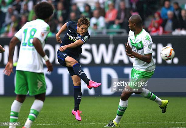 Genki Haraguchi of Berlin vies with Dante and Naldo of Wolfsburg during the Bundesliga match between VfL Wolfsburg and Hertha BSC at Volkswagen Arena...