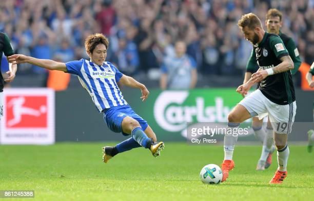 Genki Haraguchi of Hertha BSC foults Guido Burgstaller of FC Schalke 04 during the game between Hertha BSC and Schalke 04 on october 14 2017 in...