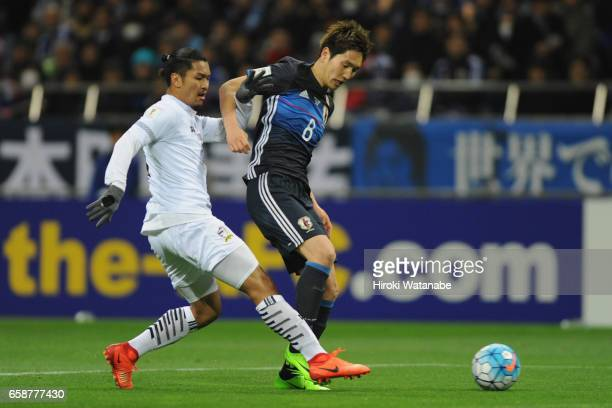 Genki Haraguchi of Japan and Adison Promrak of Thailand compete for the ball during the 2018 FIFA World Cup Qualifier match between Japan and...