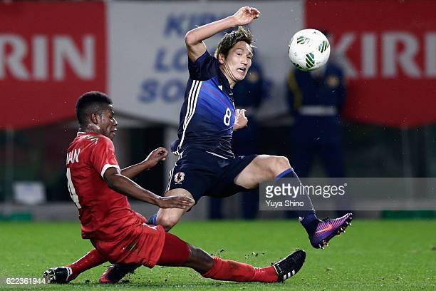 Genki Haraguchi of Japan and Nadir Awadh Bait Mabrook of Oman compete for the ball during the international friendly match between Japan and Oman at...
