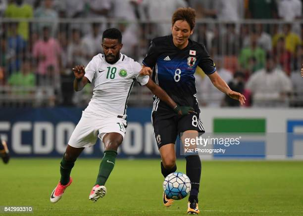 Genki Haraguchi of Japan and Nawaf Al Abid of Saudi Arabia compete for the ball during the FIFA World Cup qualifier match between Saudi Arabia and...