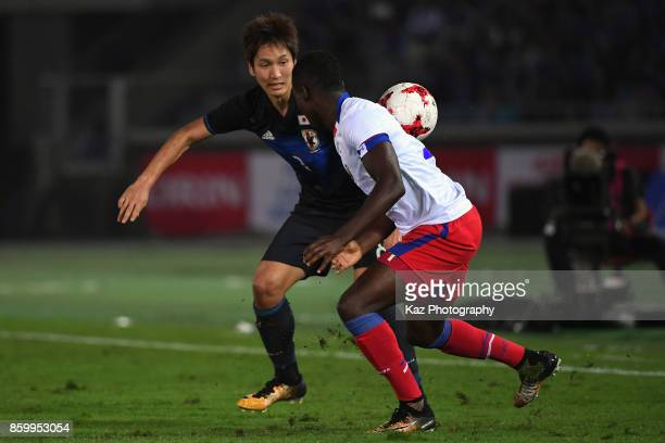 Genki Haraguchi of Japan and Richelor Sprangers of Haiti compete for the ball during the international friendly match between Japan and Haiti at...