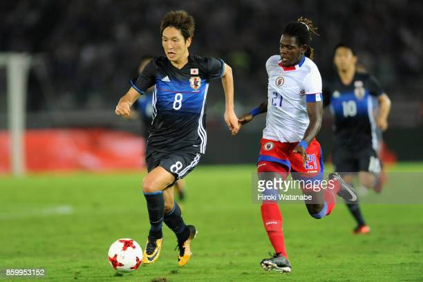 Genki Haraguchi of Japan and Samuel Maedochee Pompe of Haiti compete for the ball during the international friendly match between Japan and Haiti at...