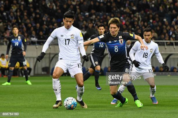 Genki Haraguchi of Japan and Tanaboon Kesarat of Thailand compete for the ball during the 2018 FIFA World Cup Qualifier match between Japan and...