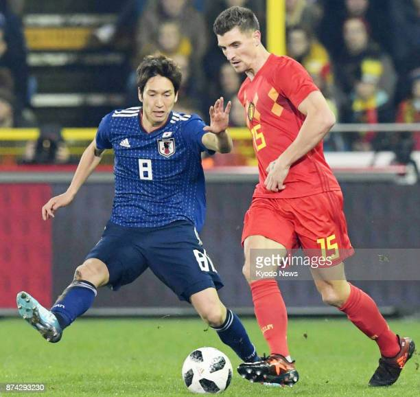 Genki Haraguchi of Japan and Thomas Meunier of Belgium vie for the ball during the first half of a soccer friendly in Bruges Belgium on Nov 14 2017...
