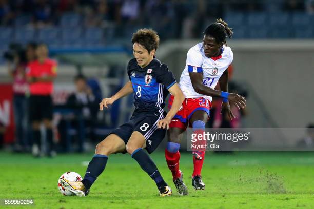 Genki Haraguchi of Japan controls the ball under pressure of Samuel Maedochee Pompe of Haiti during the international friendly match between Japan...