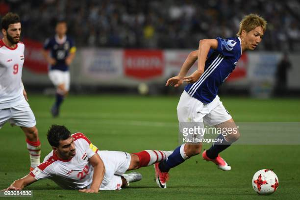 Genki Haraguchi of Japan dribbles the ball under the pressure from Khaled Almbayed of Syria during the international friendly match between Japan and...