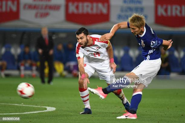 Genki Haraguchi of Japan shoots the ball under the pressure of Tamer Hag Mohamad of Syria during the international friendly match between Japan and...