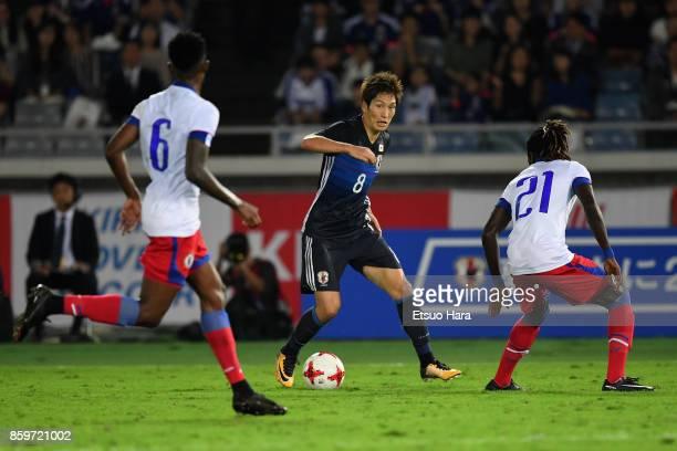 Genki Haraguchi of Japan takes on Samuel Maedochee Pompe and Renald Metelus of Haiti during the international friendly match between Japan and Haiti...
