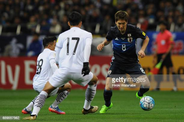 Genki Haraguchi of Japan takes on Tanaboon Kesarat and Chanathip Songkrasin of Thailand compete for the ball during the 2018 FIFA World Cup Qualifier...