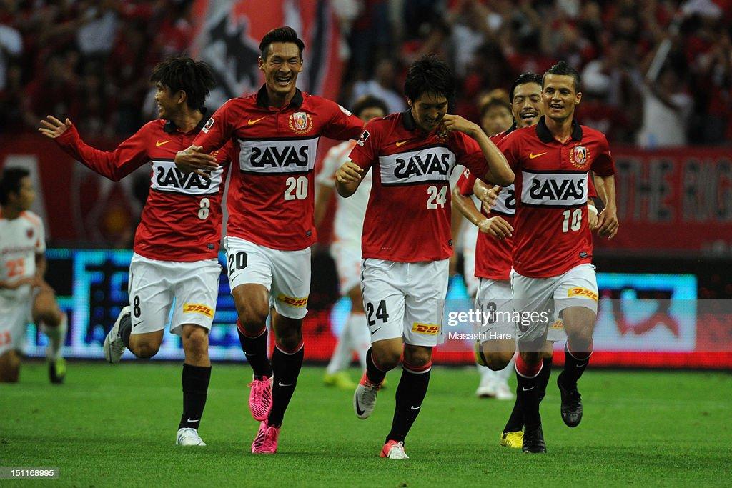 Genki Haraguchi (3L) of Urawa Red Diamonds celebrates scoring their first goal withi his team mates Yosuke Kashiwagi (1L), <a gi-track='captionPersonalityLinkClicked' href=/galleries/search?phrase=Tomoaki+Makino&family=editorial&specificpeople=775804 ng-click='$event.stopPropagation()'>Tomoaki Makino</a> (2L) and Marcio Richardes (1R) during the J.League match between Urawa Red Diamonds and Omiya Ardija at Saitama Stadium on September 1, 2012 in Saitama, Japan.