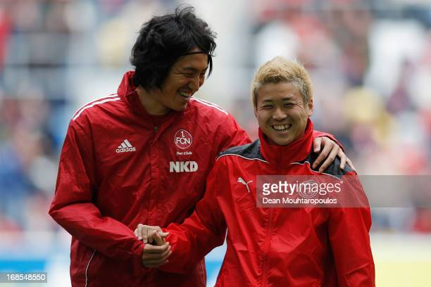 Genki Omae of Fortuna Duesseldorf and Mu Kanazaki of FC Nuernberg shake hands and have a laugh prior to the Bundesliga match between Fortuna...