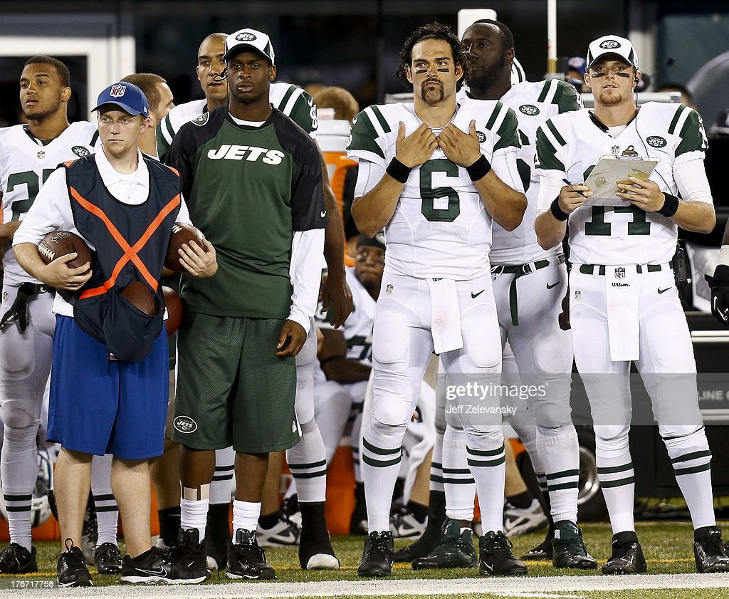 Geno Smith #7, Mark Sanchez #6 and Greg McElroy #14 of the New York Jets look on from the sidelines during their preseason game against the Jacksonville Jaguars at MetLife Stadium on August 17, 2013 in East Rutherford, New Jersey.