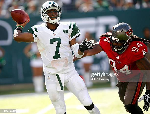 Geno Smith of the New York Jets passes under pressure from Adrian Clayborn of the Tampa Bay Buccaneers during their game at MetLife Stadium on...