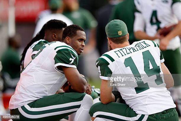 Geno Smith of the New York Jets talks to Ryan Fitzpatrick on the sidelines during their game against the Oakland Raiders at Oco Coliseum on November...