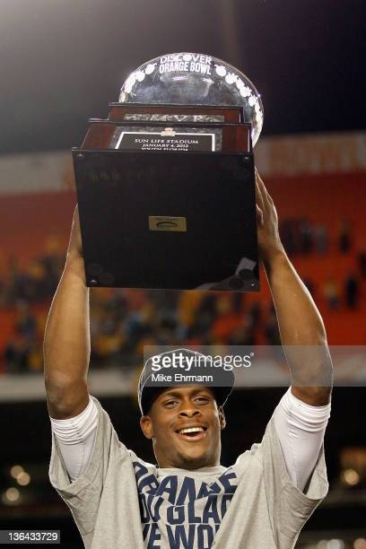 Geno Smith of the West Virginia Mountaineers celebrates with the trophy after they won 7033 against the Clemson Tigers during the Discover Orange...