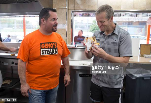 Geno Vento looks on while Dave Walder of the Newcastle Falcons eats his cheesesteak at Geno's Steaks on September 14 2017 in Philadelphia Pennsylvania