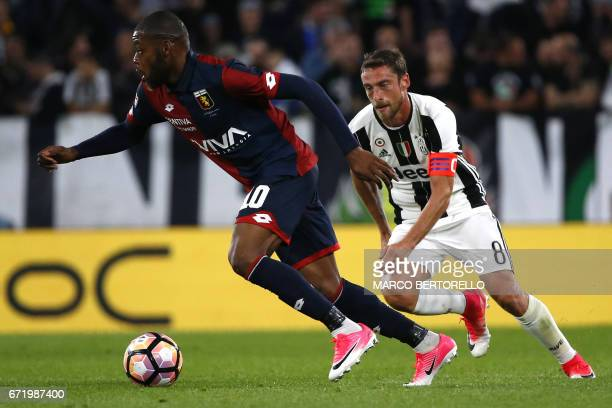 Genoa's midfielder Olivier Ntcham from France fights for the ball with Juventus' midfielder Claudio Marchisio during the Italian Serie A football...