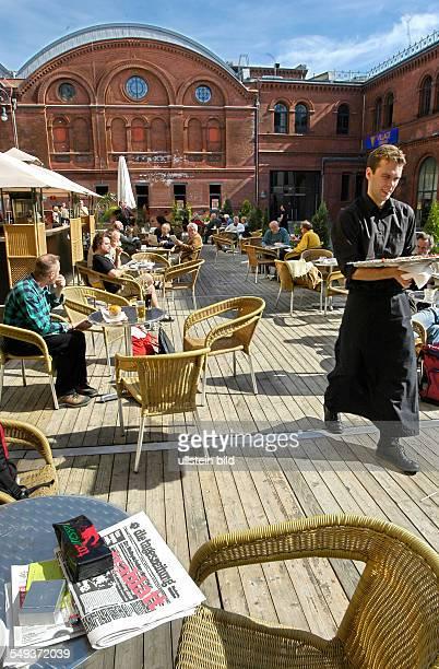 TAZ Genossenschaftsversammlung 2004 Genossen in der Pause beim Lesen der TAZ im Sommergarten der Kulturbrauerei in Berlin