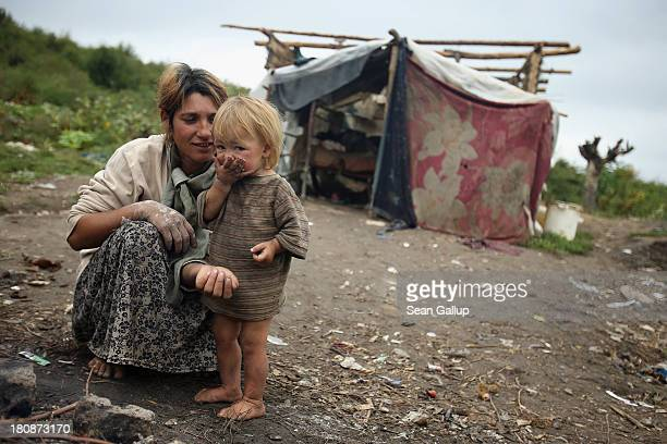 Genoveva Lingurar who is pregnant feeds her son Alexandru a potatoe baked in a campfire outside the makeshift and temporary home she shares with her...