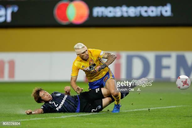 Genta Miura of Gamba Osaka tackles Crislan of Vegalta Sendai during the JLeague J1 match between Vegalta Sendai and Gamba Osaka at Yurtec Stadium...