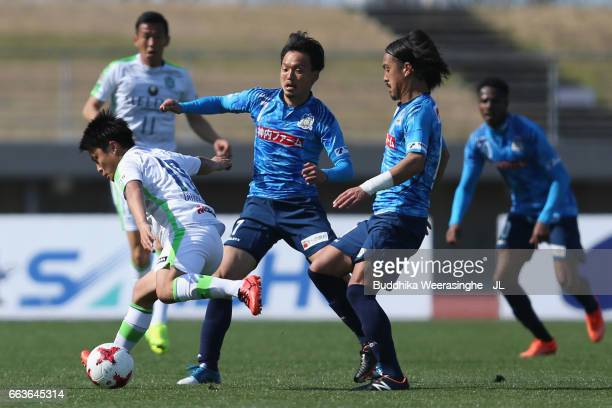 Genta Omotehara of Shonan Bellmare controls the ball under pressure of Ryota Nagata and Kenji Baba of Kamatamare Sanuki during the JLeague J2 match...