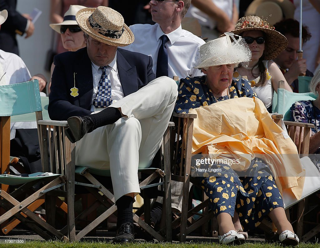 A gentleman and lady sitting in the Stewards' Enclosure take a nap whilst watching the racing on day four of the Henley Royal Regatta on July 6, 2013 in Henley-on-Thames, England.