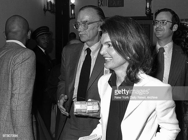 Gentleman carries the orange juice as he escorts Jacqueline Kennedy Onassis back to her seat during intermission at City Center