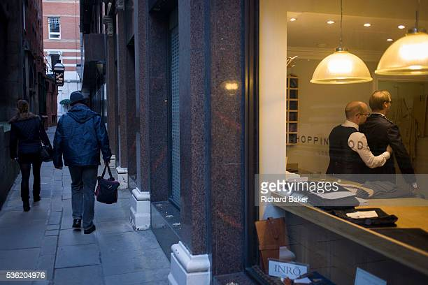 A gentleman client has a fitting for a new madetomeasure suit seen through a City taylor's window Feeling under the arm of his client the taylor...