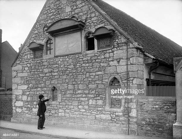 A gentleman examines a blocked window in the gable wall of the Christ's Hospital almshouses Abingdon Oxfordshire c1860c1922 The building dates from...
