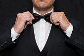 Close-up of a gentleman wearing Black Tie straightens his bowtie.