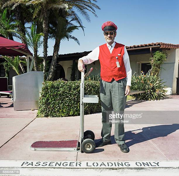 A gentleman Sky Cap stands in front of the terminal building at Santa Barbara Municipal Airport California USA Wearing his red wastecoat ID badge and...