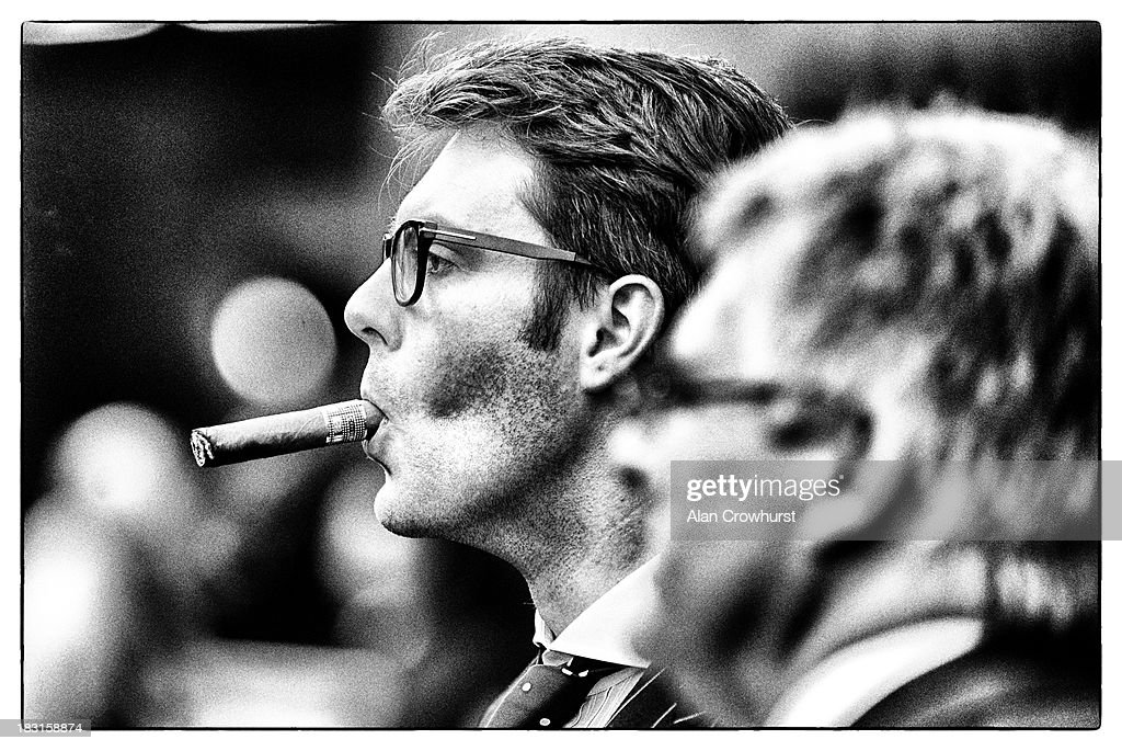 This image was processed using digital filters) A gentleman smokes a cigar at Ascot racecourse on October 05, 2013 in Ascot, England.