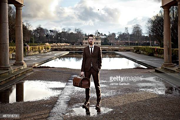 Gentleman standing in a park with a boating pond