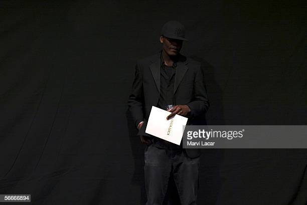 A gentleman stands behind the stage backdrop of the Luca Luca fashion show during Olympus Fashion Week held at New York's Bryant Park on February 6...